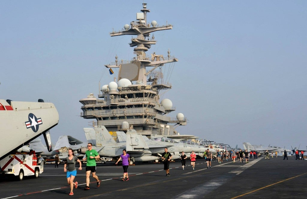 Sailors run on the flight deck aboard the aircraft carrier. (Photo: U.S. Navy photo by Mass Communication Specialist 3rd Class Margaret Keith)