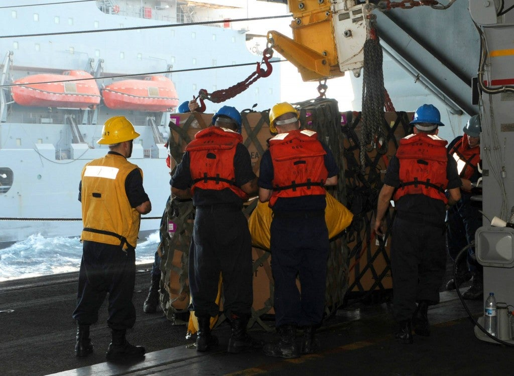 Sailors detach a pallet from a pulley during a replenishment-at-sea. (Photo: U.S. Navy photo by Mass Communication Specialist 3rd Class Margaret Keith)(Photo: