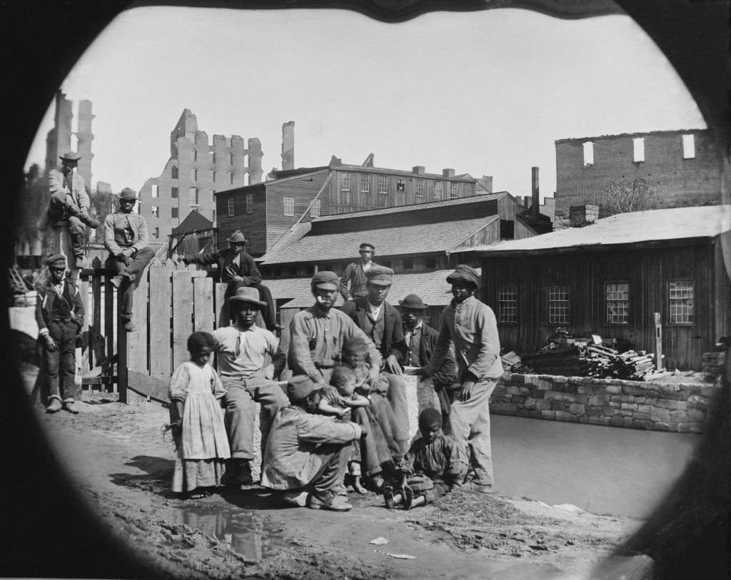 A newly freed African American group of men and a few children posing by a canal against the ruins of Richmond, Va.  Photo made after Richmond was taken by Union troops on April 3, 1865. (Photo: Everett Collection/Newscom)
