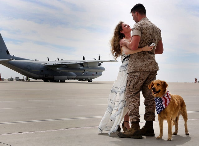 Cpl. Daniel G. Dillender, airframes mechanic with Marine Aerial Refueler Transport Squadron (VMGR) 352, Marine Aircraft Group 11, 3rd Marine Aircraft Wing, is reunited with his wife, Angelica Dillender, and their dog Bella at Marine Corps Air Station Miramar, Calif. (Photo: Sgt. Keonaona C. Paulo/ Released)
