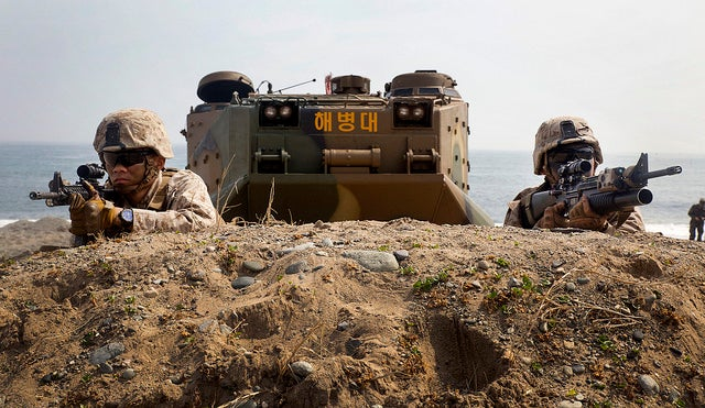 Marines wait for the command to advance after rushing out of a Republic of Korea Marine amphibious assault vehicle. (Photo: Lance Cpl. Cedric R. Haller II/Released)