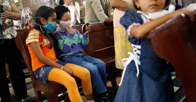 'Can get out of hand real quickly': Children in Mexico City wear surgical masks in 2009 to guard against the swine flu at a time when cases were confirmed in 18 countries. (Photo: Joe Raedle/Getty Images)
