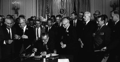 President Lyndon Johnson, watched by Martin Luther King, Jr. signing the Civil Rights Act, July 2, 1964. (Photo: Newscom)