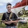 An armed pro-Russian separatist stands guard near a piece of the wreckage of the