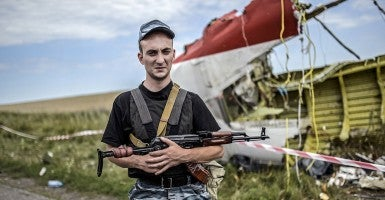 An armed pro-Russian separatist stands guard near a piece of the wreckage of the Malaysia Airlines Flight 17. (Photo: Bulent Kilic/Getty Images/Newscom)