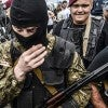 Armed pro-Russian separatists block the way to the crash site of M