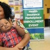 A mother holds her child while waiting to sign up for health i