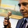 President Barack Obama holds a bobblehead doll of himself in the Outer Oval Office.