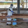 A nurse from Liberia sprays preventives to disinfect the waiting area for visitors at the ELWA Hospital where a US doctor Kent Bradley is being quarantined in the hospitals isolation unit having contracted the Ebola virus, Monrovia, Liberia. (Phot