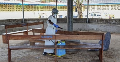 A nurse from Liberia sprays preventives to disinfect the waiting area for visitors at a hospital. (Photo: Newscom)