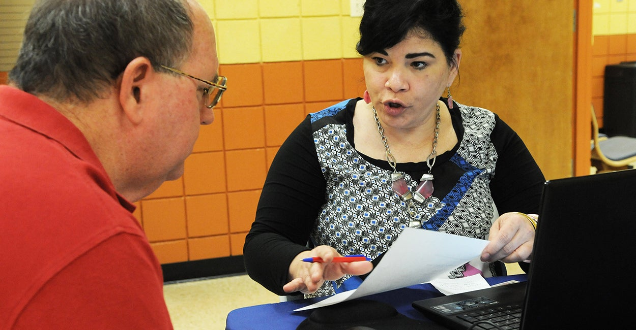 Obamacare navigator Nilda Acosta helps Richard Delph sign up for health insurance under the Affordable Care Act at the Dover Shores Community Center in Orlando. (Photo: Polaris/Newscom)