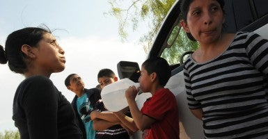 A Central American boy drinks water from a jug following his surrender to U.S. Border Patrol agents after illegally entering the United States from Mexico. (Photo: Paul Hennessy/Polaris/Newscom)