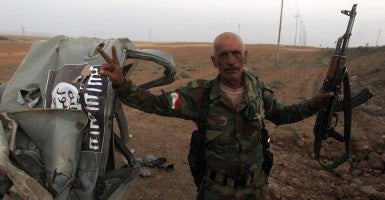 A Peshmerga fighter flashes the sign for victory next to the remains of a car, bearing an image of the trademark jihadist flag, which reportedly belonged to Islamic State (IS) militants after it was targeted by an American air strike in the village of Baqufa, north of Mosul, on August 18, 2014. Kurdish peshmerga fighters backed by federal forces and US warplanes pressed a counter-offensive Monday against jihadists after retaking Iraq's largest dam, as the United States and Britain stepped up their military involvement. (Photo: Newscom)