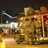 An armored vehicle carries police officers in tactical gear dow