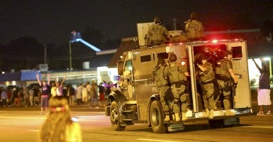 An armored vehicle carries police officers in tactical gear down West Florissant Avenue in Ferguson. (Photo: Timothy Tai/Newscom)
