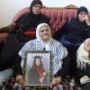 Wasfiyeh Idris, mother of suicide bomber Wafa Idris, surrounded by other female family members, holds a portrait of her daughter at her home in the al-Amari refugee camp near the West Bank town of Ramallah. According to evidence presented at a terrorism trial today, families of suicide bombers received payment