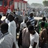 People gather near burnt vehicles as other stand on a fire truck at the site of a bomb explosion that rocked the busiest roundabout near the crowded Monday Market in Maiduguri, Borno State, on July 1, 2014. A truck exploded in a huge fireball killing at least 15 people on July 1 in the northeast Nigerian city of Ma