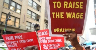 Fast-food workers hold placards in support to an increase of the fast-food workers minimum wage in New York, May 15, 2014.  (Photo: Emmanuel Dunand/Newscom)