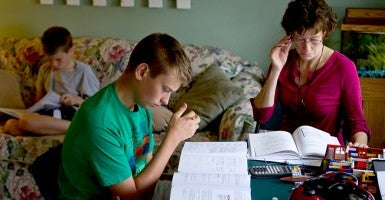 Shane McGregor, 12, left, and Bruce, 17, work in the living room on their coursework while their mother and teacher, Deanna, reviews more curriculum for her children's homeschooling. (Photo: Ken Harper/Creative Commons)