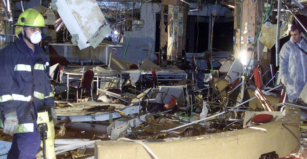 Rescue workers look over the damaged hotel in the Israeli seaside resort of Netanya, March 27, 2002.  (Photo: Havakuk Levison/Reuters/Newscom)