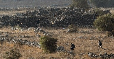 Rebels fighting the Syrian regime take position Sept. 2 near the Israeli-Syrian border. (Photo: Newscom)