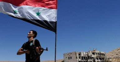 A fighter stands under a Syrian national flag in the historic Christian town of Maaloula, north of Damascus, the site of intense battles between the Syrian army and rebel groups. (Photo: Xinhua/Zhang Naijie/Newscom)