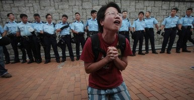 A protester kneels in front of police officers asking protesters to pray for Hong Kong as police push their way through human wall formed by pro-democracy students. (Photo: Frank Li/Newscom)