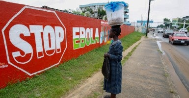 A woman looks at an Ebola sensitization mural in Monrovia, Liberia. (Photo: Ahmed Jallanzo/EPA/Newscom)