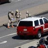 Emergency workers in hazmat suits work in a Pentagon parking lot after a woman who recently traveled to Africa vomited there, i