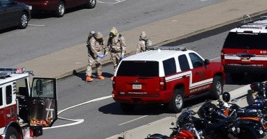 Emergency workers in hazmat suits work in a Pentagon parking lot after a woman who recently traveled to Africa vomited there, in Washington October 17, 2014. (Photo: Reuters/Kevin Lamarque)