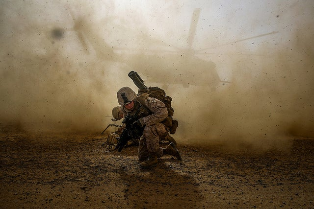 Cpl. Daniel Hopping, assaultman, Weapons Company, 1st Battalion, 7th Marine Regiment, shields himself from dust being kicked up from a CH-53E Super Sea Stallion lifting off during a mission in Helmand province, Afghanistan. (Photo: Cpl. Joseph Scanlan/Released)
