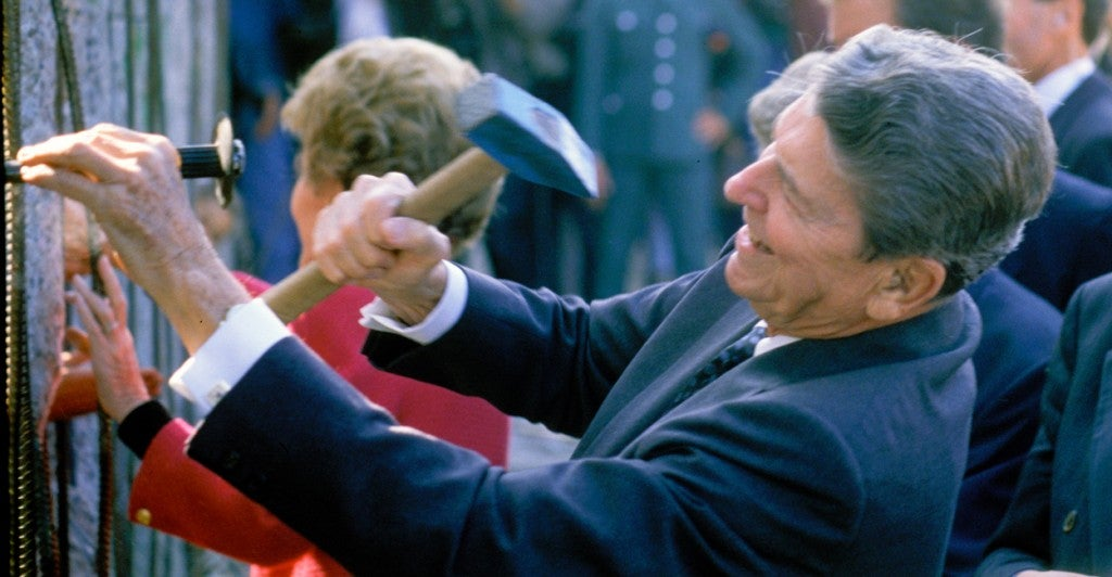 President Ronald Reagan, with his wife Nancy Reagan, hammers symbolically at an opening in the Berlin Wall, Sept. 10, 1990. (Photo: Andrew Popper/Polaris/Newscom)
