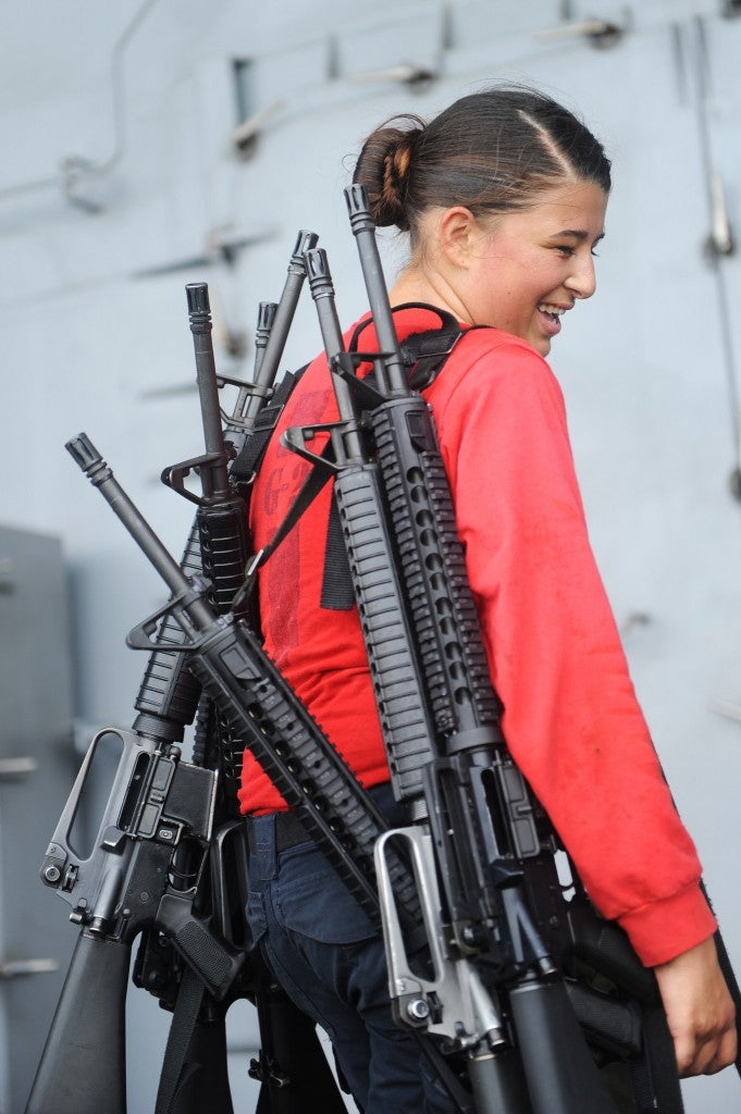 In the Arabian Gulf on Aug. 14, 2014, Gunner's Mate Seaman Coren Demastus, from Fort Smith, Ark., carries rifles after training aboard the aircraft carrier. (Photo: U.S. Navy photo by Mass Communication Specialist 3rd Class Brian Stephens)