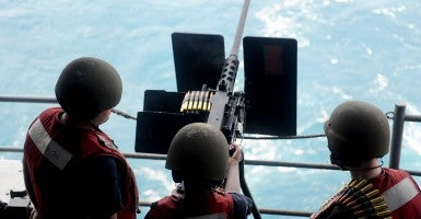 Sailors fire a .50 caliber machine gun aboard the aircraft carrier USS George H.W. Bush (CVN 77) in the Arabian Gulf on August 14. (Photo: U.S. Navy photo by Mass Communication Specialist 3rd Class Brian Stephens)