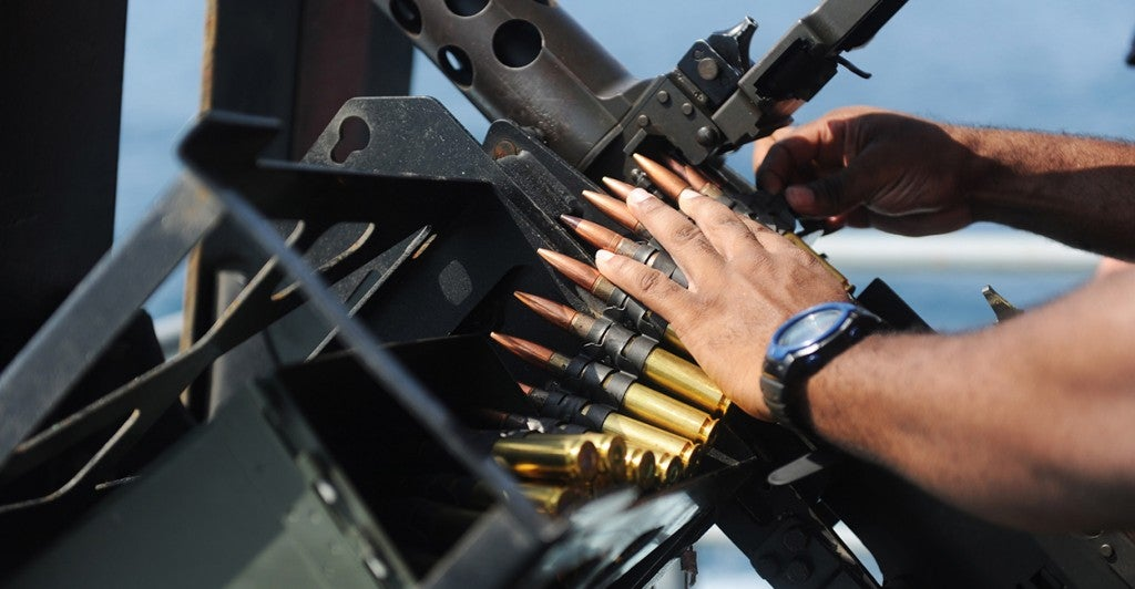 A Sailor loads a .50 caliber machine gun. (Photo: U.S. Navy photo by Mass Communication Specialist 3rd Class Brian Stephens)