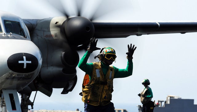 "Aviation Boatswain's Mate (Equipment) 2nd Class Lawrence Baiden, from Ghana, signals that an E-2C Hawkeye, attached to the ""Bear Aces"" of Carrier Airborne Early Warning Squadron (VAW) 124, is ready to launch. (Photo: U.S. Navy photo by Mass Communication Specialist 3rd Class Joshua Card)"