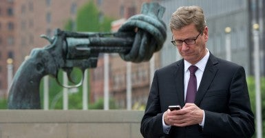 Former German Foreign Minister Guido Westerwelle stands in front of a gun with a knotted barrel, a symbol for nonviolence, at the headquarters of the United Nations in New York. (Photo: Tim Brakemeier/EPA/Newscom)