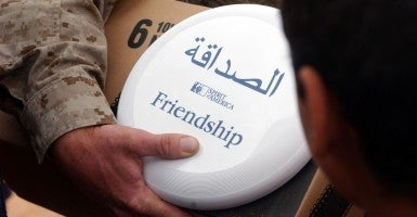 An Iraqi boy accepts a frisbee from a U.S. Marine. The frisbees were donated by the U.S.-based charity Spirit of America. (Photo: Cpl. Paula M. Fitzgerald/DOD/ZUMA Press/Newscom)