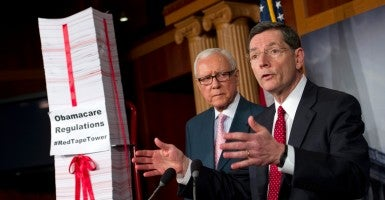 Sen. John Barrasso, R-Wyo., with Sen. Orrin Hatch, R-Utah, reveals a tower of Obamacare regulations. (Photo: Chris Maddaloni/CQ Roll Call/Newscom)
