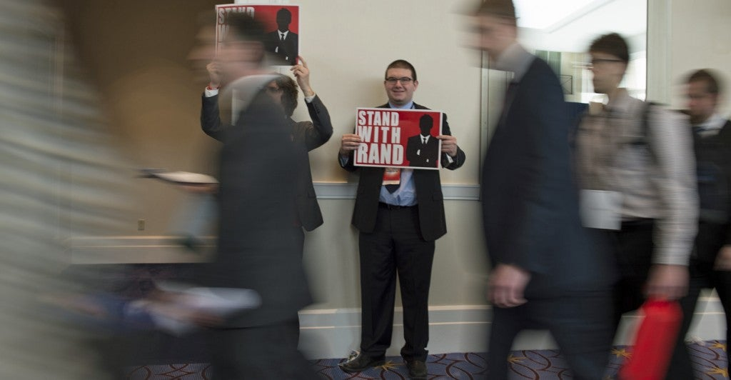 Rand Paul supporters display signs at CPAC. (Photo: Molly Riley/UPI/Newscom)