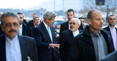 U.S. Secretary of State John Kerry and Iranian Foreign Minister Javad Zarif chat as they walk along the Quai des Bergues in Geneva, Switzerland, on January 14, 2015, during a break in their negotiations about the future of Iran's nuclear program. (State Department/Sipa USA/Newscom)