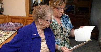 81-year-old Fay Fernandez with her daughter Debera Fathke going over paperwork. (Photo: Joan Barnett Lee/ZUMA Press/Newscom)