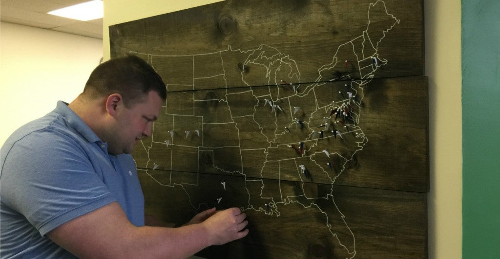 Peter Somerville, StreetShares' director of investor relations, adds a pin to a map of the United States that shows where a new borrower is located. (Photo: Melissa Quinn)