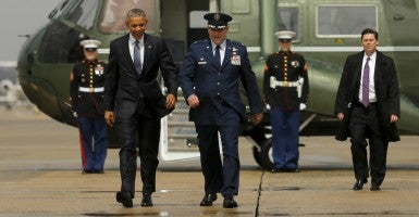 President Obama walks with U.S. Air Force Colonel John Millard, commander of the 89th Airlift Wing. (Photo: Jonathan Ernst/Reuters/Newscom)