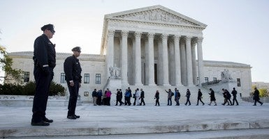 Police watch as members of the public enter the Supreme Court before the court heard arguments about gay marriage. (Photo: Joshua Roberts/Reuters/Newscom)