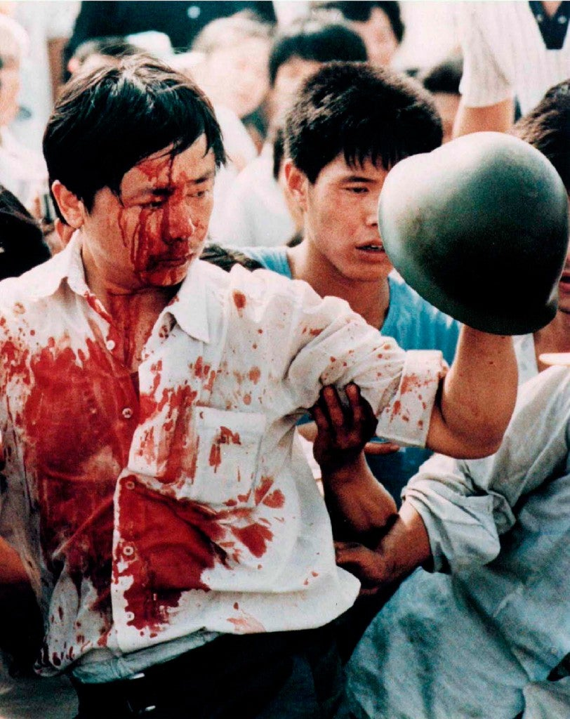 A blood-covered protester holds a Chinese soldier's helmet following violent clashes with military forces during the 1989 pro-democracy demonstrations in Beijing's Tiananmen Square. (Photo: STRINGER/REUTERS/Newscom)