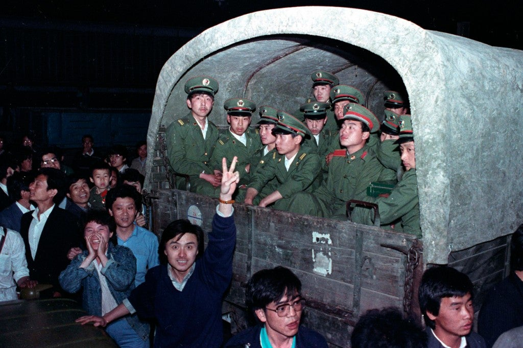 Residents of Beijing surround an army convoy of 4,000 soldiers in a suburb of the city to prevent them from continuing to Tiananmen Square, where the pro-democracy students are, in this May 20, 1989 photo. (Photo: STRINGER/REUTERS/Newscom)