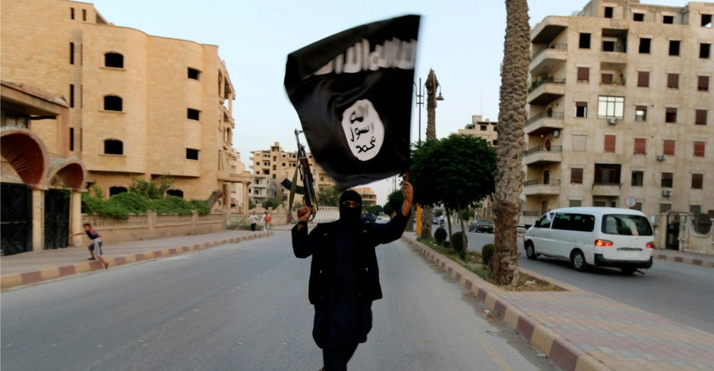 A member of ISIS waves its flag in Raqqa, Syria. (Photo:Stringer/Reuters/Newscom)