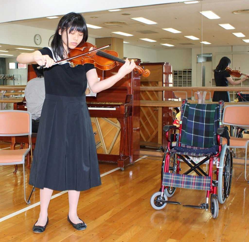 Yui Ito, a Japanese teenager, is a victim of the HPV vaccine Cervarix. In this photo from Oct. 12, 2013, she performs at an audition in Tokyo. Yui, who has suffered partial paralysis and pain since 2011, uses a wheelchair except when in bed, but  stands to play when performing. (Photo: Kyodo/Newscom)