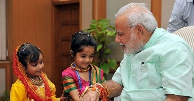 "A child ties sacred threads to Indian Prime Minister Narendra Modi on the occasion of ""Raksha Bandhan"" festival in New Delhi, India. (Photo: Press Information Bureau Xinhua News Agency/Newscom)"